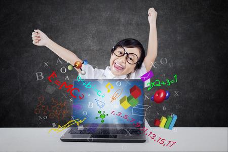 Studente femminile allegro della scuola elementare che solleva le mani nella classe con la formula di scienza, di per la matematica e di fisica sullo schermo del computer portatile