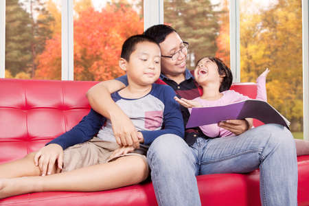 asian children: Portrait of two children and their father reading a book on the sofa, shot with autumn background on the window
