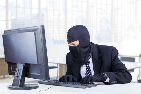 scammer: Male burglar wearing mask and steal information on the computer in the office