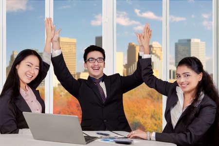 manos aplaudiendo: Retrato de tres empresarios multirraciales alegre celebraci�n de su �xito y aplaudiendo las manos juntas en la oficina