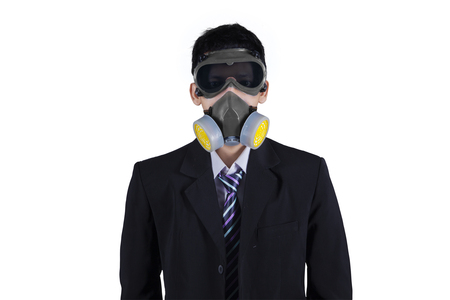 masquerader: Young businessman wearing formal suit and a gas mask in the studio, isolated on white background Stock Photo