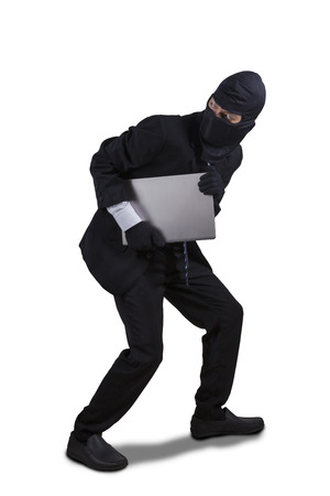 looter: Male thief wearing mask and running while carrying a laptop computer, isolated on white background
