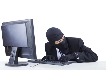 to steal: Male robber wearing mask and steal information on the computer while looking at around him