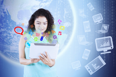 charts graphs: Young woman using a digital tablet with social media icons and background of globe Stock Photo