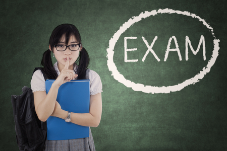 school exam: Female high school student making silence sign with Exam word on the blackboard Stock Photo