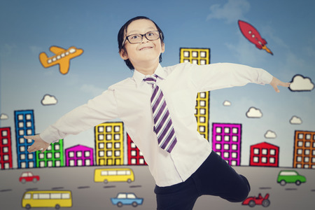 innovating: Portrait of cheerful little boy with city background. Success and creative concept Stock Photo