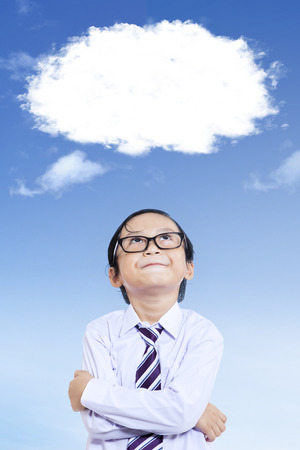 Portrait of little schoolboy thinking idea while looking up at empty speech bubble Stock Photo