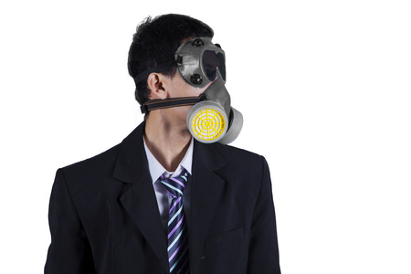 masquerader: Photo of a young businessman wearing a gas mask and formal suit in the studio, isolated on white background
