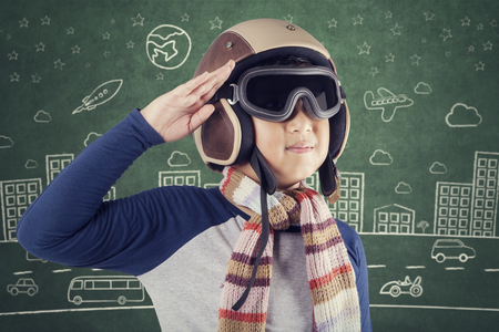 Portrait of a male child wearing an aviator helmet and giving respectful gesture with blackboard background Stock Photo