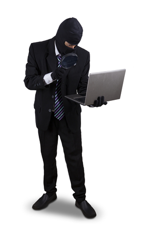 scammer: Male thief using magnifying glass to find information on the laptop, isolated on white background
