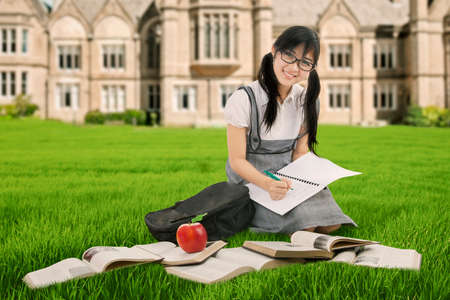 school yard: Portrait of a pretty schoolgirl smiling at the camera while studying on the grass with books at the school yard Stock Photo