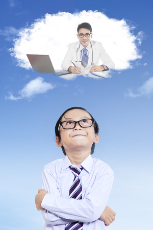 imagines: Portrait of little child imagines future job as a doctor while looking at speech bubble, shot outdoors Stock Photo