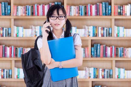 MOCHILA: estudiante de secundaria femenina bonita que habla en el teléfono móvil mientras está de pie en la biblioteca