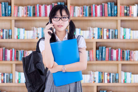 backpacks: Pretty female high school student talking on the mobile phone while standing in the library Stock Photo