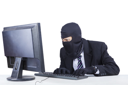 Male thief wearing mask and steal information on the computer while typing on the keyboard and looking at the monitor