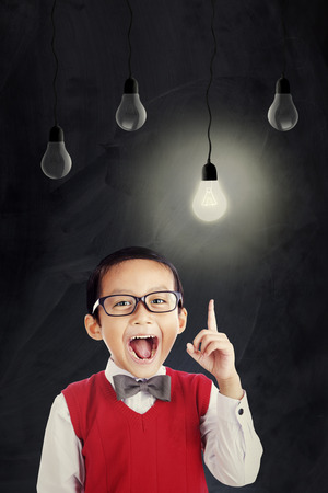 brilliant: Portrait of attractive schoolboy wearing uniform and glasses while pointing at bright lightbulb