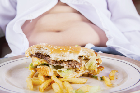 Close up of a half hamburger on the plate with fat belly of a boy Stock Photo