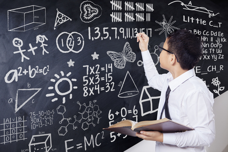 complicated: Little boy writing mathematics formula on the chalkboard while holding a book in the classroom
