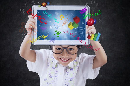 Cute little girl smiling at the camera while holding a digital tablet with formula of science, math, and physics on the screen