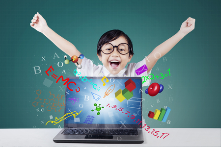 school children: Image of a cheerful little girl raising hands with formula of math on the laptop screen