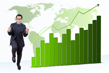 filipino people: Portrait of happy young businessman expressing his success in front of growing financial statistics Stock Photo
