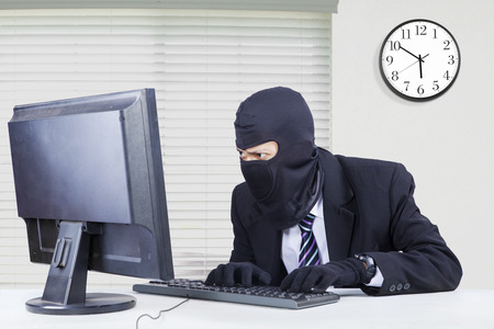 Male hacker wearing mask and steal data on the computer while typing on the keyboard and looking at the monitor