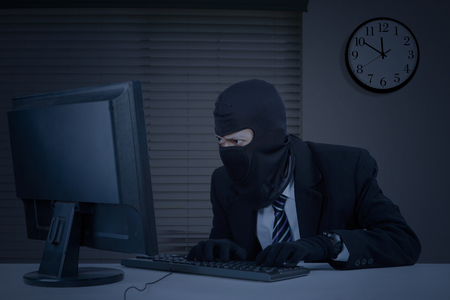 Male thief wearing mask and steal information on the computer in the office at night Stock Photo