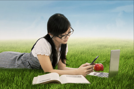 sky and grass: Pretty female college student lying on the meadow while studying with books and texting on her smartphone