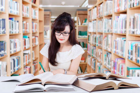 assignments: Photo of a smart female student sitting in the library while doing assignments and reading books to the source of her task