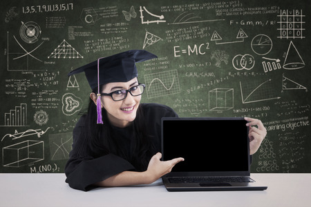 screen shot: Asian graduate in graduation gown pointing at copyspace on laptop screen. shot in classroom