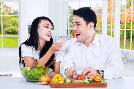 eating salad: Portrait of young couple eating vegetables salad together in the kitchen at autumn season Stock Photo