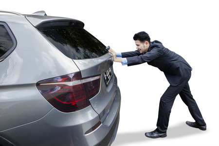empty tank: Young businessman wearing formal suit and push a car with empty fuel tank, isolated on white background