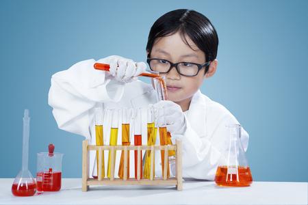 investigando: Atractivo pequeño químico con bata blanca y haciendo investigación química en el laboratorio
