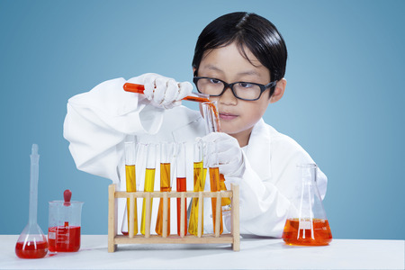 Attractive little chemist wearing white coat and doing chemistry research in the laboratory