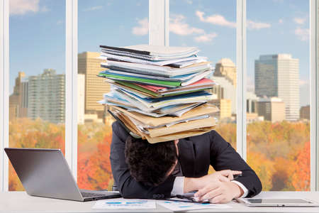 above head: Image of tired businessman sleeping on the table with a pile of documents on his head, shot in the office Stock Photo