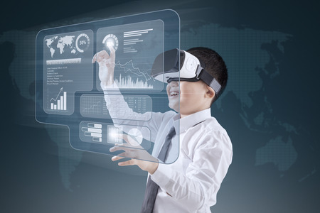 Little boy wearing virtual reality headset while touching financial graph on the virtual screen