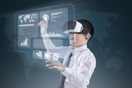 Weinig jongen die virtual reality headset terwijl het aanraken van financiële grafiek op het virtuele scherm Stockfoto