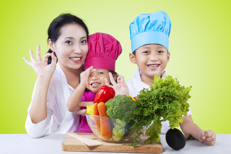 asian lifestyle: Portrait of mother and her children showing perfect sign with fresh vegetables on the table, shot with green background