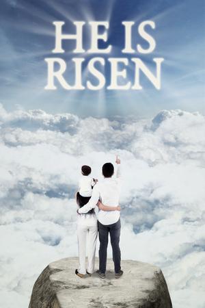 familia cristiana: Imagen de la familia cristiana feliz que se coloca en la montaña y mirar el texto ha resucitado en el cielo