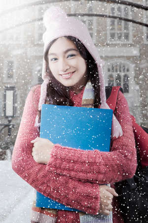 school yard: Cute female high school student wearing winter clothes and smiling at the camera with snowfall at school yard