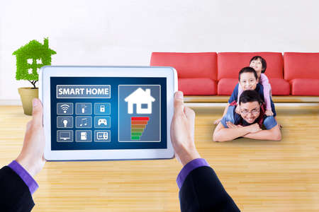 screen shot: Picture of controller applications of smart home system on the digital tablet screen. Shot with happy father and his children lying on the floor at home