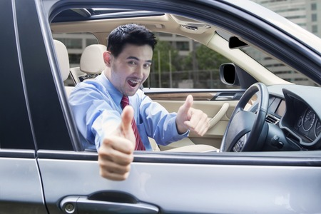Cheerful young man showing thumbs up while driving a new car on the road