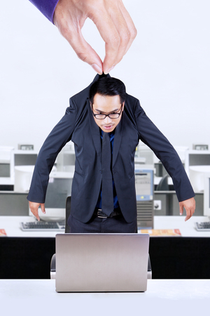 Hand lifting a male employee and put him in the office with laptop on desk