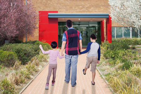 holding hands while walking: Image of young man walking with his children to school while holding hands