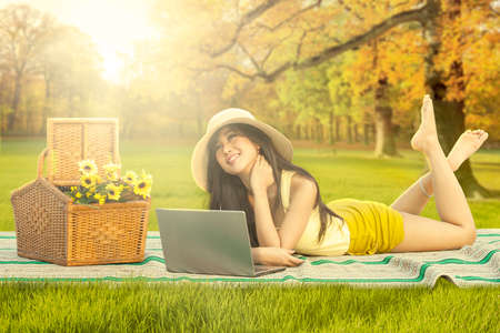 woman lying: Image of a cute young woman relaxing at the autumn park while lying on mat with laptop and basket