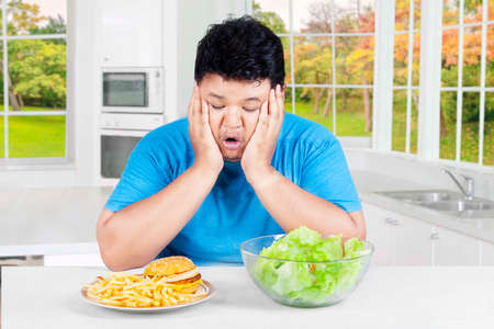choose person: Overweight Asian person sitting in the kitchen and looks confused to choose hamburger or salad Stock Photo