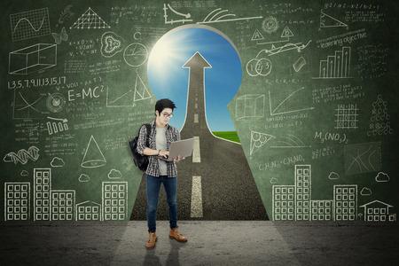 personas de pie: Imagen de un estudiante universitario de sexo masculino utiliza un ordenador portátil mientras está de pie delante de un ojo de la cerradura