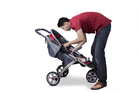 perambulator: Portrait of a young man and his baby inside a stroller, isolated on white background