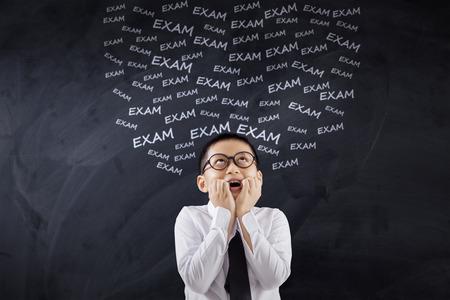 Retrato de un estudiante de escuela primaria frustrados pensando que su examen en el aula Foto de archivo