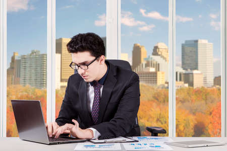 formalwear: Photo of young businessman wearing formalwear working with laptop in the office near the window